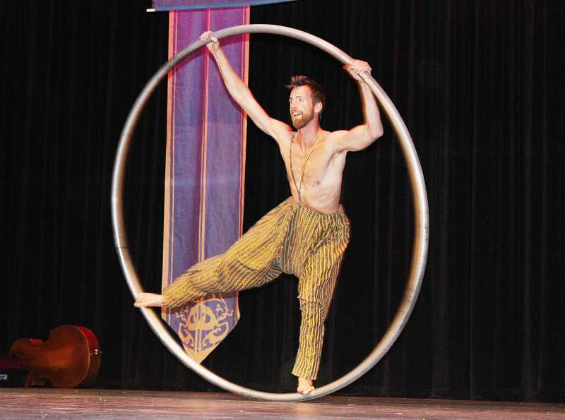 HOLLY M. GILL - Hoola hoop performer Ty Vennowitz does acrobatics with a giant hoola hoop.
