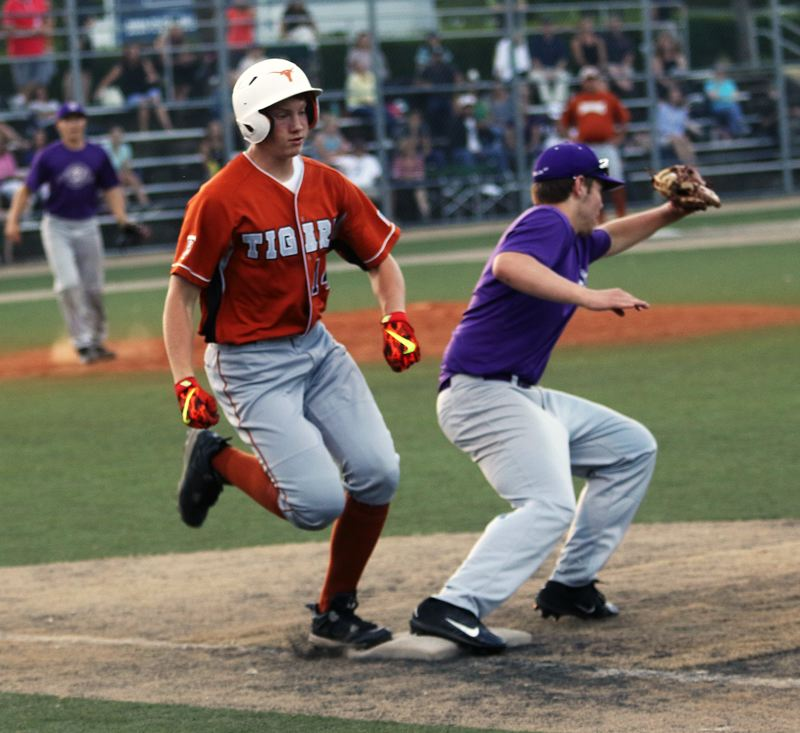 DAN BROOD - Tigard's Fletcher Ahl (left) races to first base during the Longhorns' game with Sunset.