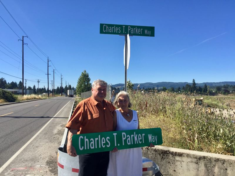 PHOTO COURTESY OF DI SAUNDERS - Scott and Gail Parker hold a sign for Charles T. Parker Way in Scappoose.