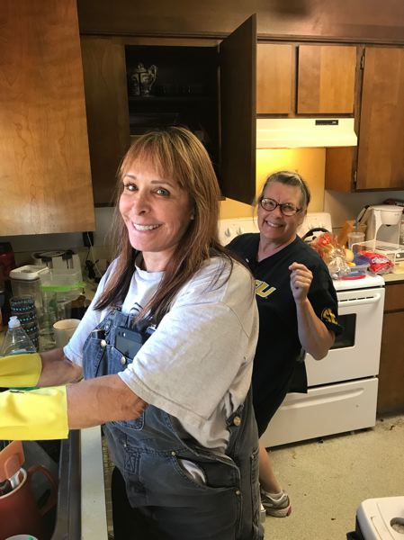 PHOTO COURTESY OF ANDY MCCANDLESS - Penny Jarigese and Cindy Roberts help clean a St. Helens woman's kitchen Sunday, July 16 as volunteers for Michelle's Love. The organization helps single mothers battling cancer with small comforts like house cleaning, meals and financial assistance if needed.