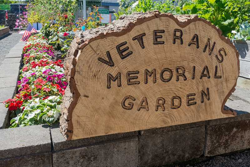 NEWS-TIMES PHOTO: CHRISTOPHER OERTELL - A tree carving welcomes veterans and all others into the new addition to the Demonstration Gardens at the Washington County Fair Complex in Hillsboro.
