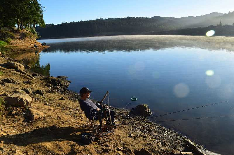 HILLSBORO TRIBUNE FILE PHOTO: CHASE ALLGOOD - A fisherman waits for a catch on the banks of Hagg Lake in 2016. The lake has claimed several lives in the last few years, including a 68-year-old Hillsboro man on July 30.