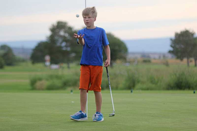 WILL DENNER/MADRAS PIONEER - Ashton Carl, 11, tosses his ball in the air after sinking a putt on the No. 7 hole.