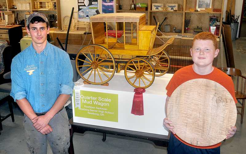 SETH GORDON - Newberg High School woodworking students Roehben Sarkisian (left) and Todd Halleman display their award-winning projects at Anvil Academy in Newberg. Sarkisian's model stagecoach earned honorable mention in the high school open division of the AWFS Fresh Wood student design competition, while Halleman's curly maple platter placed second in the high school functional category of the AAW Turning to the Future competition. Both will showcase their work Friday at Anvil Academy as part of Art Walk.