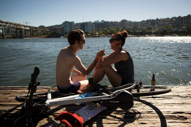 PAMPLIN MEDIA GROUP PHOTO: JAIME VALDEZ - Andrew Call and Laura Bond hangout on the docks along the east-side of the Willamette River Monday. Call and Bond who are both bartenders enjoy their day off.