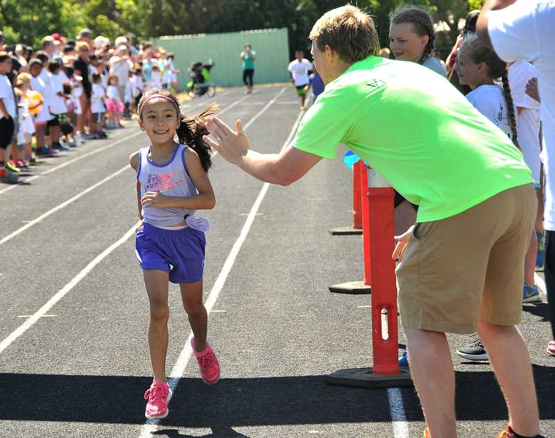 SPOKESMAN PHOTO: VERN UYETAKE - Breeanna Hollins gets a congratulatory high-five from Gordon Iversons as she finishes her race.