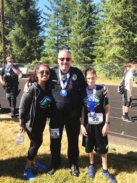 PHOTO CREDIT: RALPH PAINTER MEMORIAL 10K, 5K AND KIDS RACE - Scappoose's Eric Bunday, 38, a sergeant with the Hillsboro Police Department (118), and Rainier's Riley Painter, 13 (58) enjoy time together.