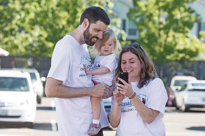 HILLSBORO TRIBUNE PHOTOS: CHRISTOPHER OERTELL - Jeff and Tamara and 18-month-old Emerson look at photos at the Prader-Willi Walk at Hillsboro High School.