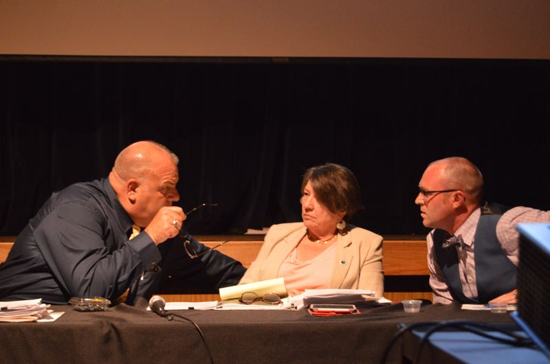 SPOTLIGHT PHOTO: COURTNEY VAUGHN - Columbia County Commissioners Henry Heimuller, Margaret Magruder and Alex Tardif confer after a lengthy public hearing Wednesday, Aug. 2, in Clatskanie. Commissioners opted to delay voting until Sept. 13.