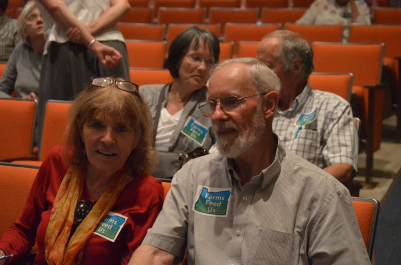 SPOTLIGHT PHOTO: COURTNEY VAUGHN - Ann Morten (left) and Darrel Whipple (right) wear stickers bearing the slogan 'farms feed us' to address county commissioners over a project that would rezone farmland in Clatskanie to use for future industrial projects.