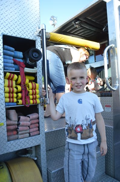 SPOTLIGHT PHOTO: COURTNEY VAUGHN - Eddy, 5, checks out a fire truck on display by Scappoose Fire District during National Night Out at Heritage Park in Scappoose.