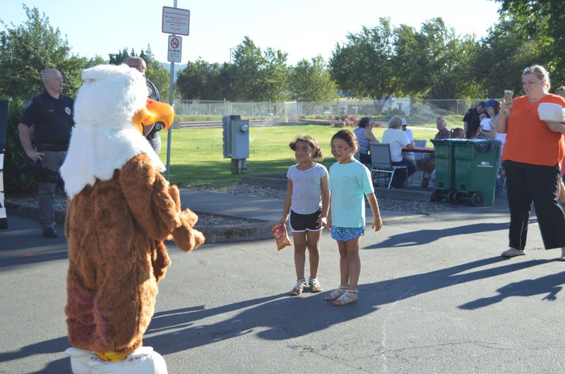 SPOTLIGHT PHOTO: COURTNEY VAUGHN - Eddie Eagle, a gun safety mascot, approaches children at Heritage Park in Scappoose during National Night Out.