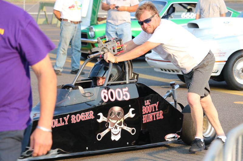 REVIEW/NEWS PHOTO: JIM BESEDA - Robert Jackson Jr., rolls 14-year-old Hunter Jackson and his junior dragster to the start line at Portland International Raceway Wednesday.