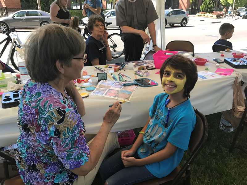 SPOKESMAN PHOTO: MADISON STATEN - Carolina Boyd gets a new look with help from the face painting booth, run by the St. Francis of the Assisi Church.