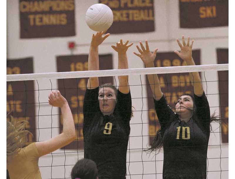 HERALD FILE PHOTO: COREY BUCHANAN - Former Canby volleyball player Mindy Wilmes (left) reaches for the volleyball during the first round of the state playoffs against Central Catholic in 2014.