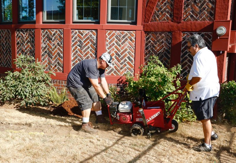 COURTESY PHOTO - Rotarians Brian York, left, and Bob Avila double-team a stump grinder during the club's effort Saturday, Aug. 5,to cleanup and beautify the historic block in downtown Gresham.