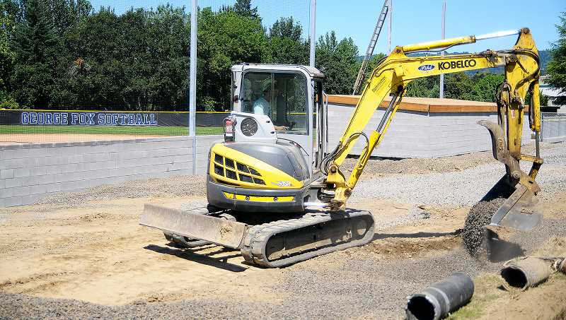 SETH GORDON -  Pihl Construction worker Austin Duyck moves gravel earlier this summer as part of the renovation of the softball stadium at George Fox University's Morse Athletic Complex. The project includes     renovated   dugouts, a new backstop and grandstands.