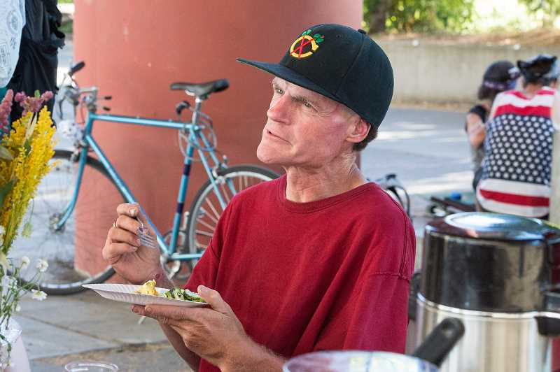 Sean, a local homeless man, inquires about some of the ingredients in his salad.