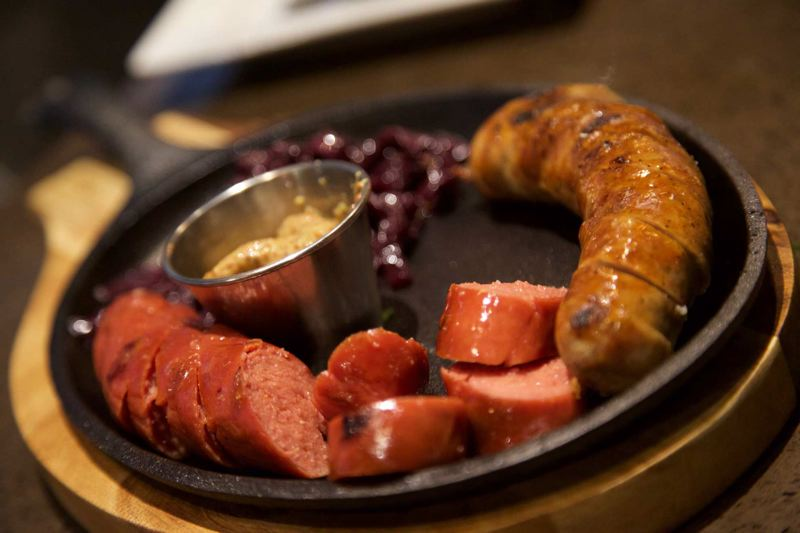 SUBMITTED PHOTO - Kehoe's $15 sampler has a variety of premium sausages with an assortment of pickled peppers, Kalamata olives, feta, red onion marmalade, stone-ground mustard and fresh pita bread.
