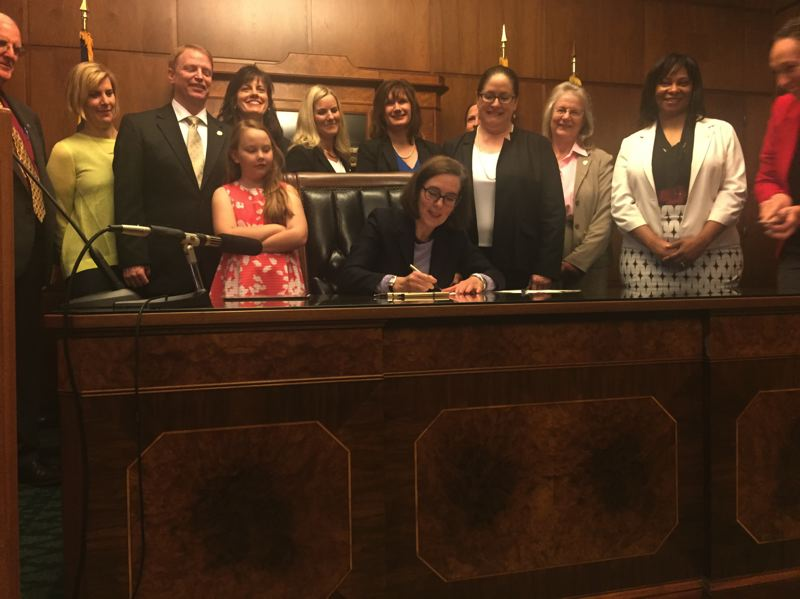 PARIS ACHEN/CAPITAL BUREAU - Gov. Kate Brown signs a pay equity bill inside her ceremonial office at the Oregon State Capitol in Salem June 1, 2017.