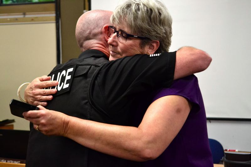 POST PHOTO: BRITTANY ALLEN - Police Chief Ernie Roberts presented City Manager Kim Yamashita, former police chief, with a retirement badge for her service.