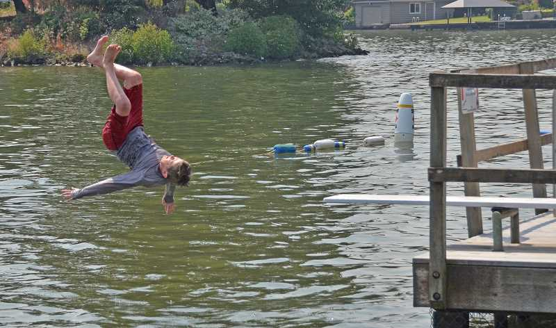 REVIEW PHOTO: VERN UYETAKE - Brandon Taliaferro enjoys leaping off the Lake Grove Swim Park diving board.