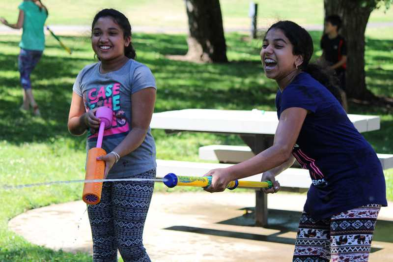 SPOKESMAN PHOTO: SAM STITES - Dwija and Vindhya Adamala douse their foes during a water fight in Murase Plaza Park on Monday, July 31 during the Wilsonville Librarys Teen Party.