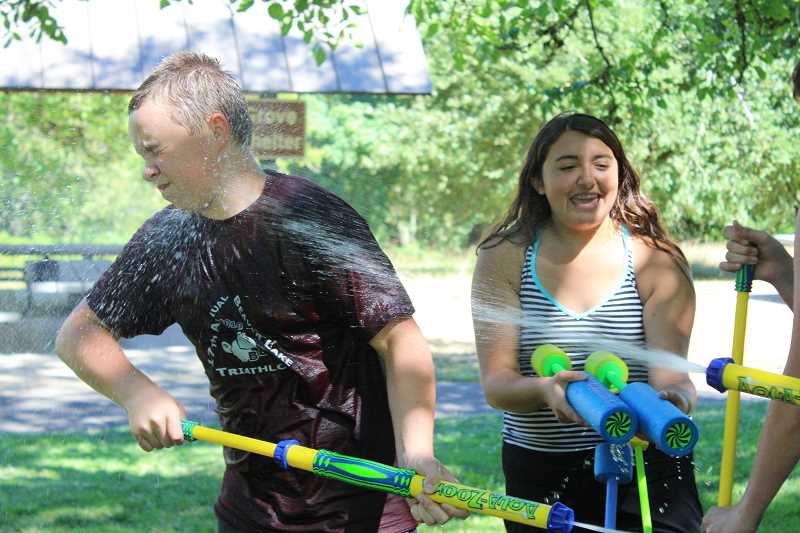 SPOKESMAN PHOTO: SAM STITES - Anthony Eisenbacher recoils as hes hit in the face from a blast of water during a water fight hosted by the Wilsonville Librarys youth services team.