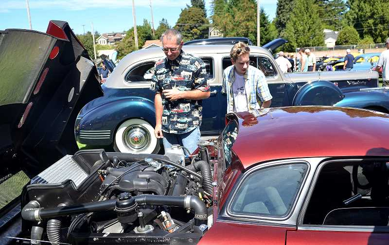 REVIEW FILE PHOTO: VERN UYETAKE - Mike and Eli Bassich check under the hood of one of the hundreds of cars on display in George Rogers Park at last year's Collector Car & Classic Boat Show. This year's event is scheduled for Aug. 26-27.