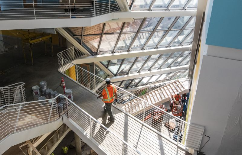 PAMPLIN MEDIA GROUP: JONATHAN HOUSE  - A worker from Skanska crosses the catwalk in the atrium at the new Karl Miller Center at Portland State University. The School of Business will open its new wing, triple the square footage of the old one, this September. Architects Behnisch Architekten and SRG Partnership wanted to make the building a welcoming place to stop when crossing the campus, a place where students and even the public can get a snack and hang out.