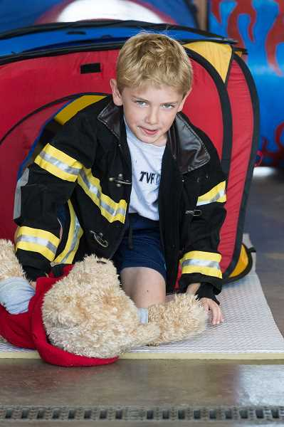 HILLSBORO TRIBUNE PHOTO: CHRISTOPHER OERTELL - Ryland Myers, 8, crawls through a tunnel to simulate staying low to avoid smoke during a fire at the TVF&R open house at Station 19.