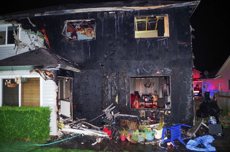 CONTRIBUTED PHOTO: GRESHAM FIRE - A one-alarm fire chewed through the vinyl siding of this two-story single-family home located on the 700 block of Southwest Burlingame Circle on Wednesday, Aug. 9, in Troutdale.