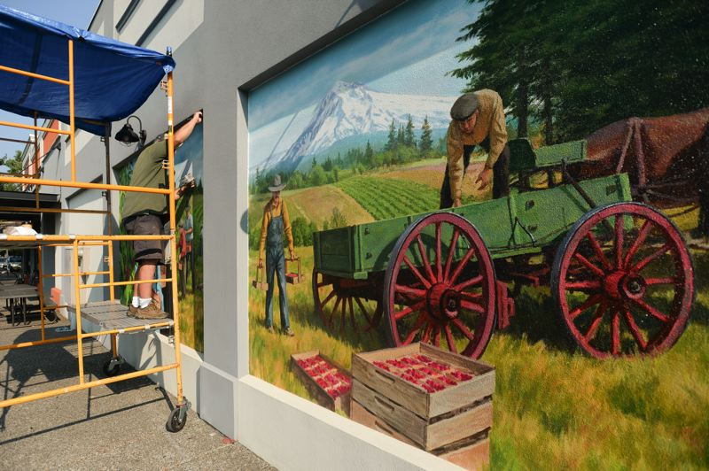 OUTLOOK PHOTO: JOSH KULLA - Muralist Don Gray wraps up the trim on his latest work in downtown Gresham celebrating the city's agricultural history. In one panel, workers load crates of berries into a wagon as Mount Hood stands watch in the background. In the other, people pick berries off their vines.