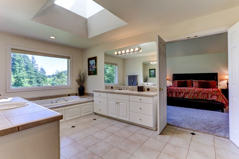 COURTESY PHOTO: LEGACY REALTY GROUP - A master suite is outfitted with double sinks, a large walk-in closet plus a walk-in shower and jetted Jacuzzi tub.