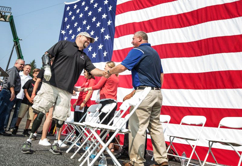 TIMES PHOTO: JONATHAN HOUSE - Retired Army veteran Wade Mitcheltree, left, shakes hands with David DeHarpport, president of Four D Construction, at the dedication of his family's new home in Tigard.