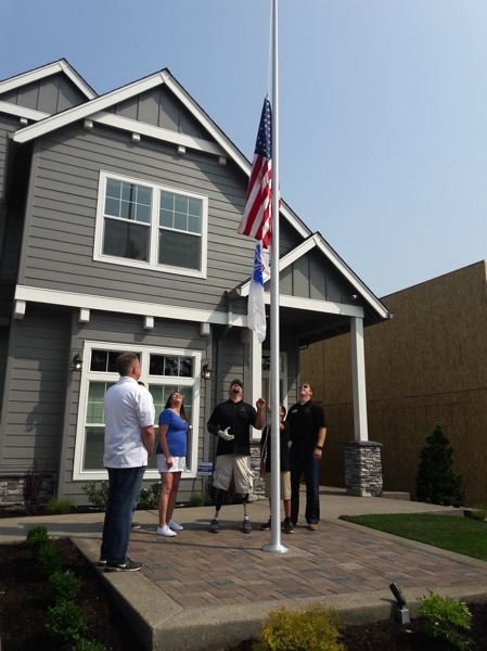 TIMES PHOTO: MARK MILLER - The Mitcheltree family raises the flags of the United States and the U.S. Army in front of their new home for the first time.