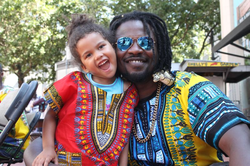 TRIBUNE PHOTO: LYNDSEY HEWITT - Valin Primus and his daughter Vada, 3, enjoyed the Pan African festival on Saturday, Aug. 12.