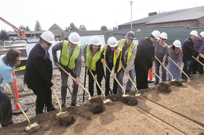DANIEL PEARSON - City officials, developer Mary Hanlon, some of her investors and interested citizens watched as The Dahlia Building officially broke ground this week.