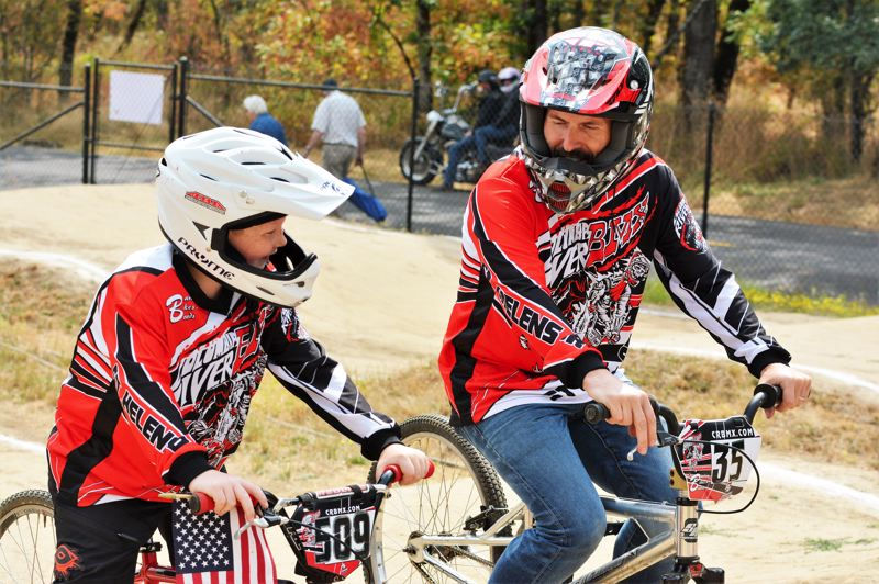 SPOTLIGHT PHOTO: JAKE MCNEAL - Travis Dunning (509), 8, of St. Helens, the 8 Novice winner, shares a laugh with Paul Barlow of hometown shop Barlow Bikes and Boards.