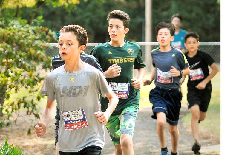 SETH GORDON - Alexander Aguilar leads a pack of runners during the 3,000-meter race that concluded the Veritas Kids Running Camp Friday at Jaquith Park.
