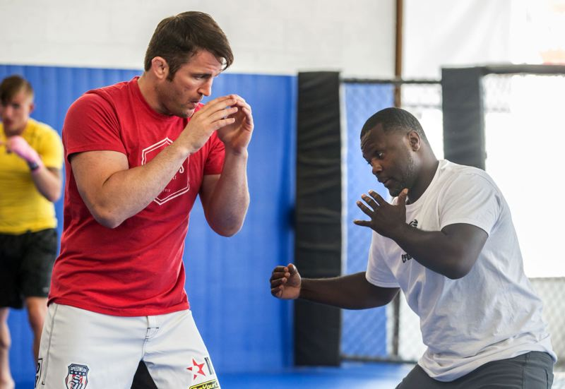 TRIBUNE PHOTO: JONATHAN HOUSE - Steve Forbes (right), who has sparred many times with boxers such as Floyd Mayweather Jr., now works out in Portland with various athletes, helping MMA star Chael Sonnen (left) and others with their form.