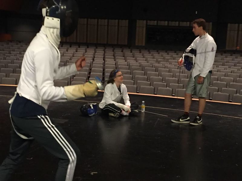 COURTESY PHOTO: JADE KEARSLEY - Scappoose High School english teacher and fencing instructor Gregory Demeaux, left, leads a drill while his son, Dylan, a freshman, and senior Ben Warren converse on the auditorium stage.
