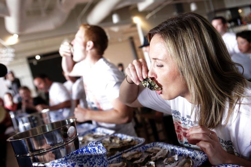 COURTESY OF WAYS & MEANS OYSTER HOUSE - Contestants eat oysters during a 'Shuck-It' challenge at Ways & Means Oyster House in Huntington Beach, Calif., last year.