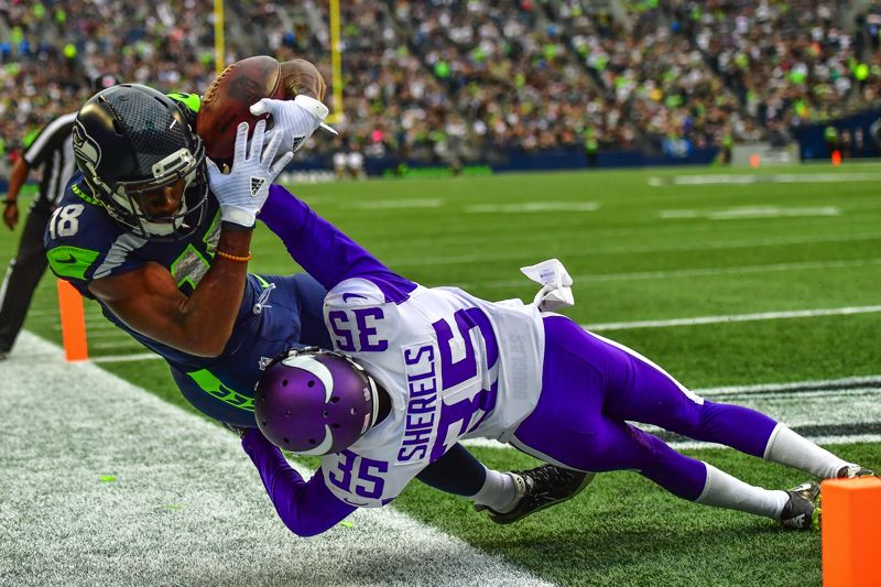 COURTESY: MICHAEL WORKMAN - Kasen Williams of Seattle goes for a reception against Marcus Sherels of Minnesota.