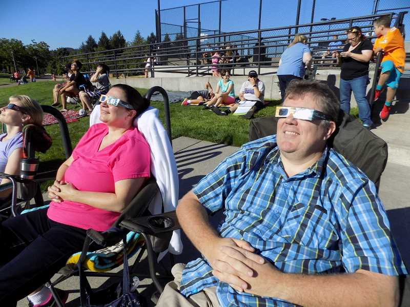 GAZETTE PHOTO: RAY PITZ - Sherwood residents Steven Bodo and his wife Mona take in the Great American Eclipse in front of the tennis courts on Aug. 21 shortly before 9:30 a.m. For both of them, it was their second eclipse, having witnessed the 1979 event from their then-home in Transylvania, Romania.