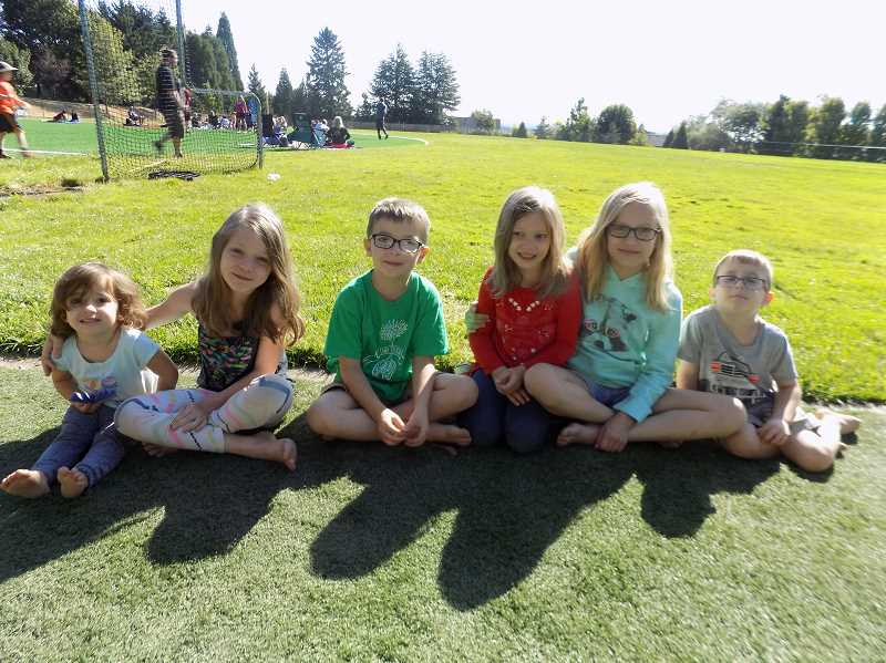 GAZETTE PHOTO: RAY PITZ - Marielle Johnson, left, Audrina Peterkin, Levi Johnson, MacKenna Peterkin, Shanelle Peterkin, Micah Johnson enjoy the eclipse from their spot on the Synder Park baseball field on Aug. 21.