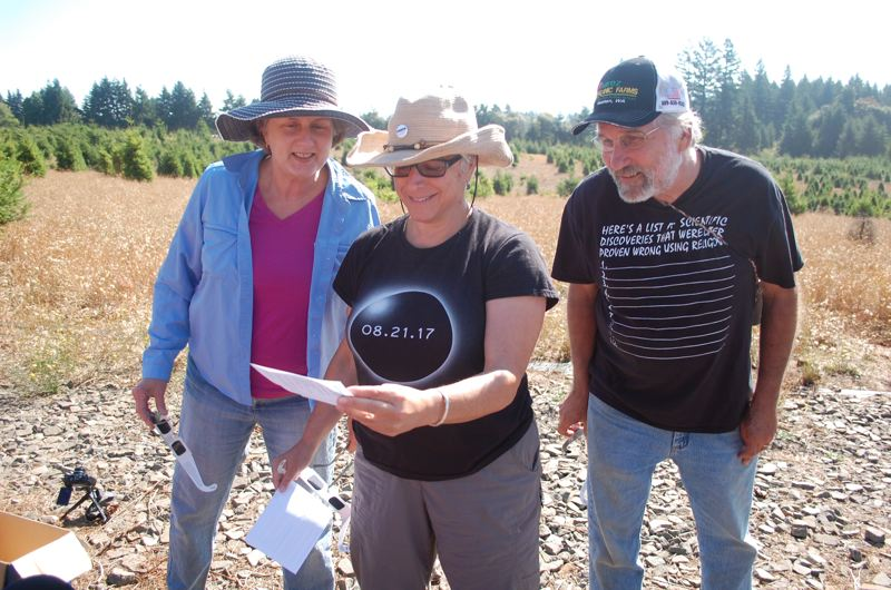 PHOTO BY RAYMOND RENDLEMAN - Seattle-area residents Sheryl Belcher (from left), Esther Howard and Bruce Hoeft check out a pinhole they made to view the Aug. 21 eclipse.