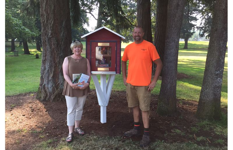 SUBMITTED PHOTO - Oregon City Women's Club member Gail Aldridge celebrates with Jason Thompson of the Oregon City Parks Department after he installed a lending library at Rivercrest Park.