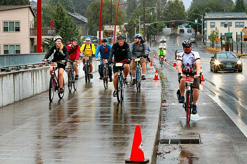 DAVID F. ASHTON - Providence Bridge Pedal participants head across the Sellwood Bridge, this year on the sidewalk and bike laneamidst the only rainy morning since mid-June! That didnt seem to bother any of the riders.