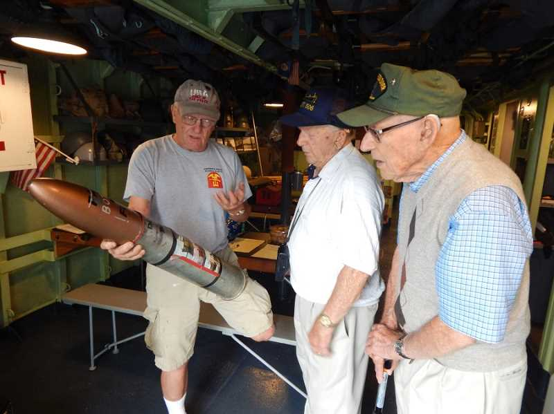 BARBARA SHERMAN - In the USS LCI (L)-713 crew mess, Mark Stevens (left), who served in the Marines and is a volunteer restoring the ship, shows Navy veterans Joe Doyon and Carl Finley a torpedo, one of hundreds of WWII artifacts that volunteers have brought onboard as part of the restoration process.